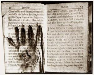 Libro di preghiere su cui è impressa un'impronta di mano. Museo delle Anime del Purgatorio, Roma.